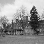 A black and white image of the Lazaretto from 2005. The building is behind a few trees that dot the landscape. The field in front of the building has a boat attached to a trailer.