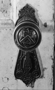 A black and white image of a doorknob at the Lazaretto. The knob and key shield have a detailed geometric design and the knob had a scale on the front.