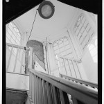 A black and white image of the cupola of the Lazaretto. The banister of the steps and the windows make up a majority of this sharp upward view.