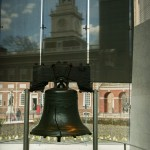 A color photograph of the liberty bell from inside the Liberty Bell Center.  Behind the liberty bell is Pennsylvania State House (Independence Hall).