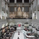 A photograph of the interior court of the former Wanamaker's store on Market Street, featuring the Grand Organ acquired from the St. Louis World's Fair of 1904.