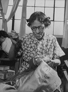 photograph of a woman stitching sleeves on an army overcoat