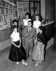 Photograph of Dick Clark surrounded by young women
