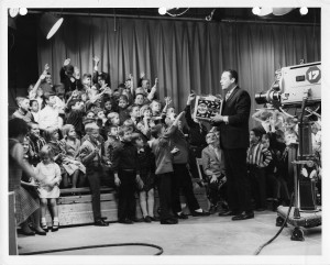 An image of Bill Webber speaking in front of cameras and an audience full of sitting and standing children.