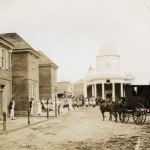 A black and white image of the Colonial High Street developed for the fairgrounds. The image is shot from the middle of the street, looking towards a dome building in the background. A house and carriage are on the cobblestone road, and there are a people walking along the sidewalk on the left side of the image. Some of the brick houses have people dresses as revolutionary war soldiers stationed outside the doors.