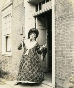 A black and white photograph of a woman in the doorway of a brick building. The image shows the entirety of the woman's dress, which consists of a circular design, a bonnet, and a neck scarf. She is holding a purse and an umbrella in her left hand.