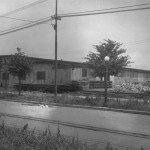 A black and white photograph of a single story wooden building that has a sign for the Vare Construction Company. The image shows a road in front of the building, as well as some trees, power lines, and streetlamps between the road and the building. Outside the building are a few large piles of stones and stacks of wood boards.