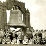 A black and white photograph of the eighty-foot liberty bell with a large crowd posed in front of it. The group posing for the photograph consists of men and women dressed in suits, dresses, and a variety of different hats. The front row of people are sitting in the grass, while the back row are standing.
