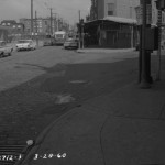 A black and white image of the intersection of Ninth, Warton, and Passyunk Ave in 1960. The streets are empty except for a few cars parked on the streets.