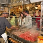 An photograph taken from behind the grill at Jim's Steaks. A chef is cooking cheese steaks while a group of people wait in line to purchase one.