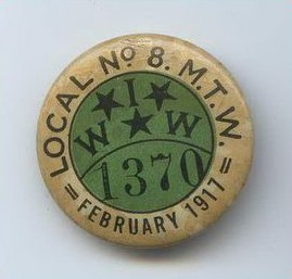 "An image of a round membership Button for the Industrial Workers of the World. The button is gold along the edge and green in the center. The outer gold ring reads ""Local No. 8. MTW February 1917. The center has the letters IWW mixed with three stars, and the number 1370."