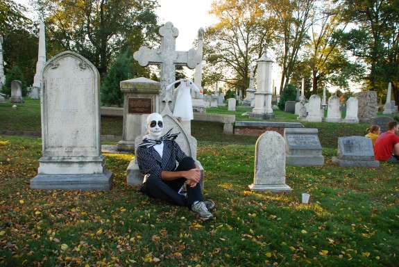 A color photograph of  a person dressed as a skeleton, sitting next to a gravestone.