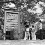 photograph of a group outside of a EMAN sign