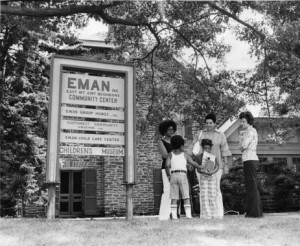 photograph of a group outside a sign for the East Mount Airy Neighbors