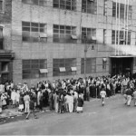 A large group of striking workers are standing outside one of the Campbell buildings; filling the sidewalk and blocking the doors of the building.