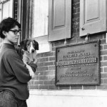 Photograph of a young woman holding a dog, outside the Morris Animal Refuge