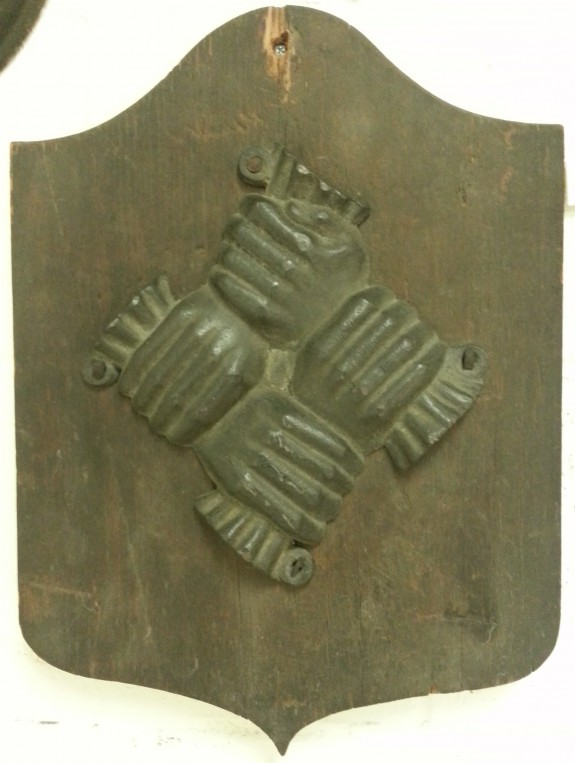 An image of the Philadelphia Contributionship Fire Mark, which has four hands interlocked. The hands are made of metal and they are mounted to a wooden board.