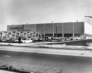 A black and white image of a Gimbels department store. A parking lot filled with vehicles and a road to enter the store's property is also depicted.