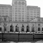 A black and whit photograph of the front of the Philadelphia Board of Education building. The image only shows the front of the building and some of the landscaping near the entrance. There is one tree to the left of the building, and a field of grass in front of the building's entrance.