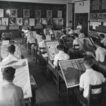 A photograph of a classroom with about eighteen students divided into four rows. Each student is sitting at their desk and they are all painting different images. A teacher is standing to the right of the students. A blackboard filled images is in the background of this image.