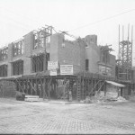 A black and white photograph of the Thomas Durham Elementary School under construction. The image shows what will be the front and left side of the building. The concrete and stone walls are semi-complete, but there are still metal bars and supports showing. Some wooden supports are along the outside of the building.