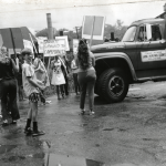 A black and white photo of a group of people holding signs in front of a truck.