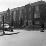 A black and white photograph of the front of four brick row houses. These row houses have elevated stoops. The road, sidewalk, and a car can be seen in front of this series of row houses.