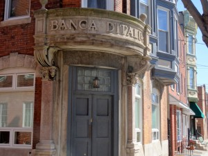 "A color photograph of the front of the Banca D'Italia building. The Words ""Banca D'Italia"" are carved into the stone above the front door. This image also shows some of the brick siding of the bank, and some of the glass windows with stone designs above them."