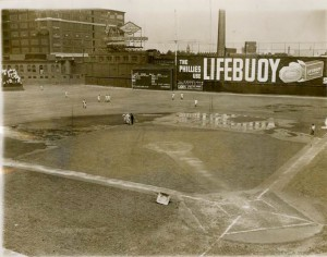 A black and white photograph of the baker bowl baseball field. The baseball diamond and field are wet with puddles around large sections of the field. A few players in uniform are running on the outfield, and to the stands on the left side of the image people are sitting. There are large brick buildings in the background and an advertising billboard for Lifebuoy soap.