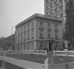A black and white photograph of the a stone building in front of a large grassy field. The image shows the rectangualr, three story building from the front and the right side of the building. There are some sidewalks and higher buildings visible on the right side of the building.