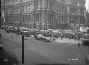A photograph from April 26, 1918 depicting a supply convoy of military supply trucks outside city hall.