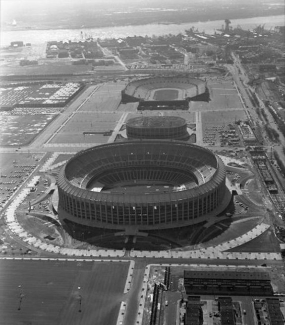 A black and white aerial photograph of three stadiums in south Philadelphia. Closest to the foreground is Veterans Stadium, followed by Spectrum Arena, and the John F. Kennedy Stadium. This image also shows the expanses of parking lots around each stadium, and some of the industrial buildings beyond those parking lots.