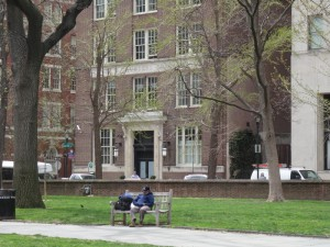 A color photograph of the brick Saunders building in the background. The foreground shows a bit of the green grass and sidewalks of Washington Square. There are a few trees, a bench, and a few people walking around the area in front of the building.