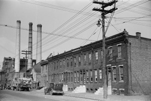 A black and white image of a  series of brick row homes. THere is a factory with three smoke stacks further down the street. A telephone pole, a car, and a truck carrying pieces of wood are in front of the houses.