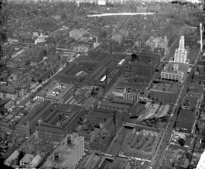 A black and white aerial image depicting a series of factory buildings surrounded by residential houses, businesses, and churches.
