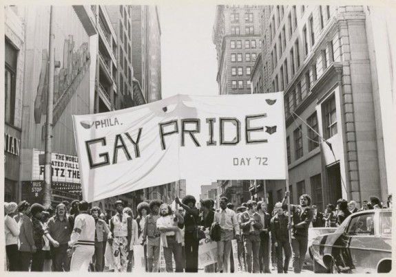 A black and white photograph of a group of people holding a large white banner with the words