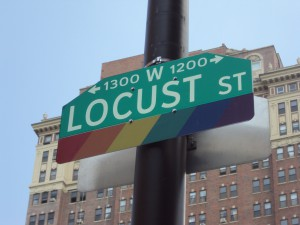 A color photograph of a street sign for Locust Street on a black pole. The green sign with white letters has an additional rainbow colored section on the bottom.