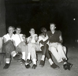 A black and white photograph of a group of five men sitting on a park bench. The background is dark, obscuring any detail. The five people on the bench show various cheerful expressions and are posing for the camera in an exaggerated manner.