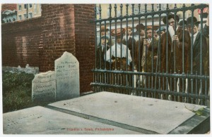 A color photograph of a group of people (many wearing hats) looking through a iron bar fence at the gravestones of Benjamin Franklin and his family. Some of the brick wall and other gravestones are visible on the left side of the image.