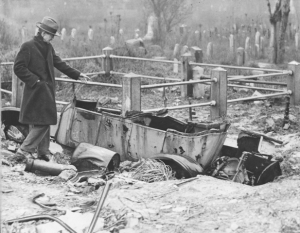 A black and white photograph of a man loking at an abandoned vehicle left in a graveyard. The grass is over gown, gravestones are knocked over, and the ground is uneven. There are also other metal parts surrounding the vehicle and scattered around through the background .