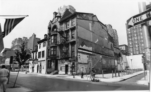 A black and white photograph of a block of buildings on Locust Street. The image shows four buildings in the foreground, whit higher buildings in the background. There are people standing and biking on the the street in front of the buildings.