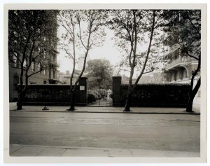 A black and white photograph of the front entrance to a cemetery. The brick walls and iron entrance are centered in the photograph. The foreground of the image shows the sidewalk and the paved street in front of the cemetery entrance. Trees are growing out of the curb of the foreground sidewalk and in the far background.