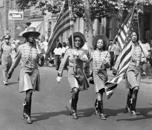 A black and white photograph depicting four African American women walking in color guard garb displaying American flags. They are walking as part of a larger parade, observers are lining the sidewalk in the background.