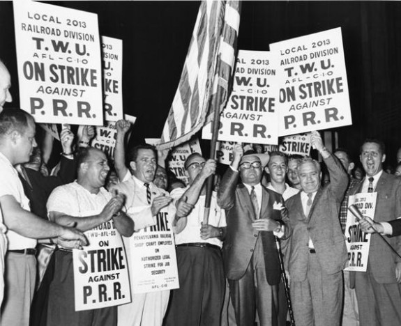 A black and white photograph of a crowd holding signs and banners displaying slogans for the strike. A man in the center of the image is holding an American flag.