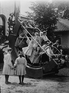 A black and white photograph of a group of children playing on a large piece of playground equipment. Two girls are standing in front of the equipment.