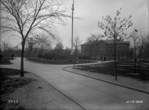 A black and white photograph of a he central garden of a park. Pathways lead to and from the central garden, and tress line the pathways.