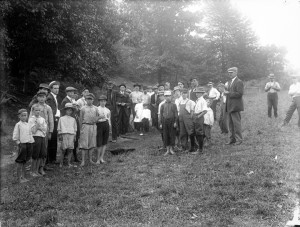 A black and white photograph of a group of children and adults standing in a field.