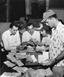 A black and white photograph of four men (three sitting and one on the right standing) looking over piles of receipts and money  on a table.