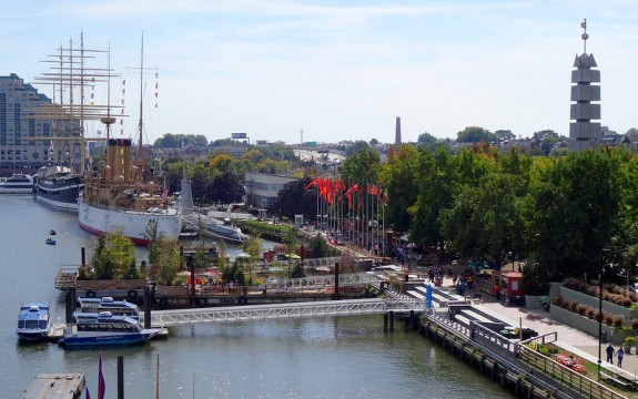 A color photograph of Penn's Landing, with ships on the water, a boardwalk with people walking on it, green trees and a steel obelisk above the treetops on the right side of the image. A older sailing ship is in the background of the image, along with more trees and buildings.