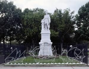 A color photograph of a white statue of Christopher Columbus standing on a base. The statue is surrounded by a black fence and and grass, with trees in the background. On the fence are the white outlines of three sailing ships.